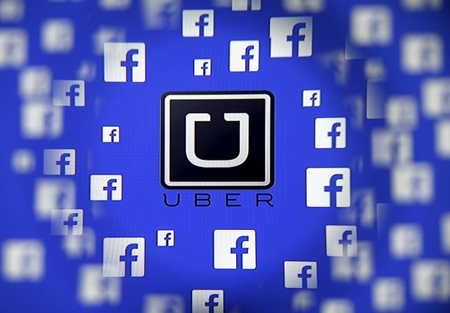 Logo of the Uber and Facebook are seen through magnifier on display in this illustration taken in Sarajevo
